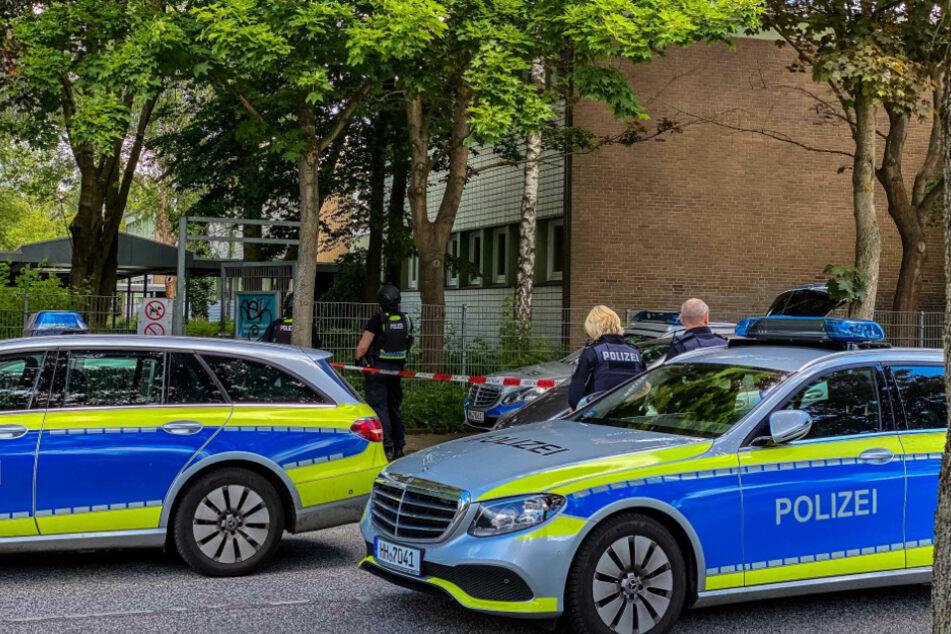 Polizeikräfte stehen vor der Schule.