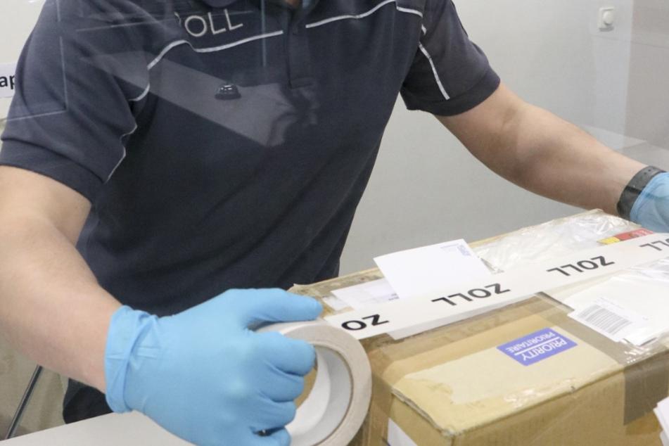 Ein Zollbeamter klebt ein geöffnetes Paket nach der Inspektion zu.