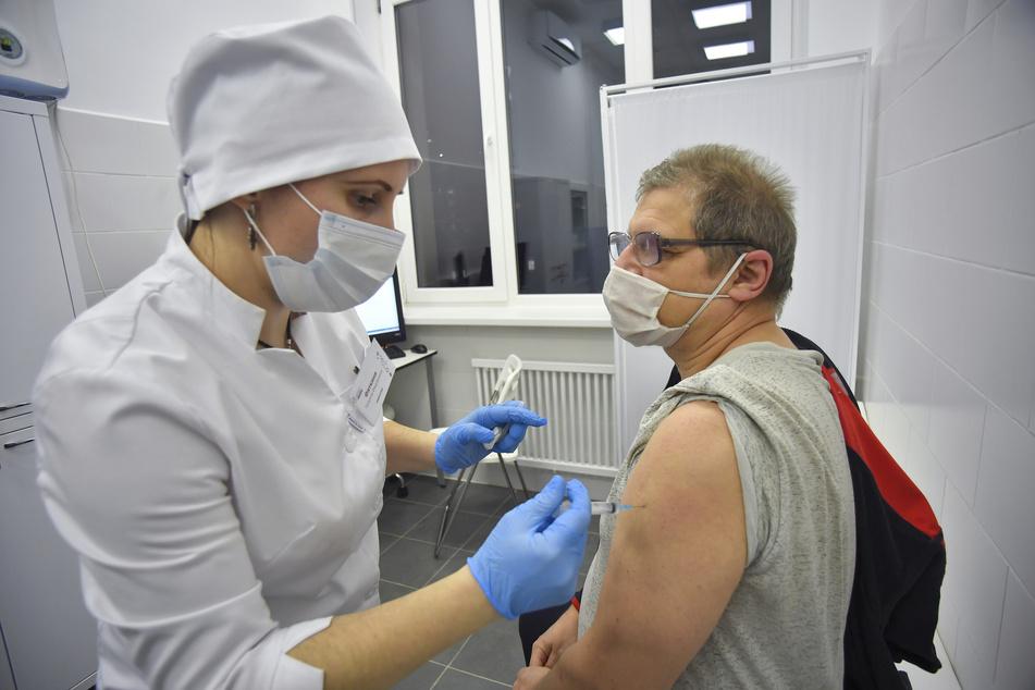Eine medizinische Mitarbeiterin verabreicht einem Mann in Moskau den Corona-Impfstoff Sputnik V.