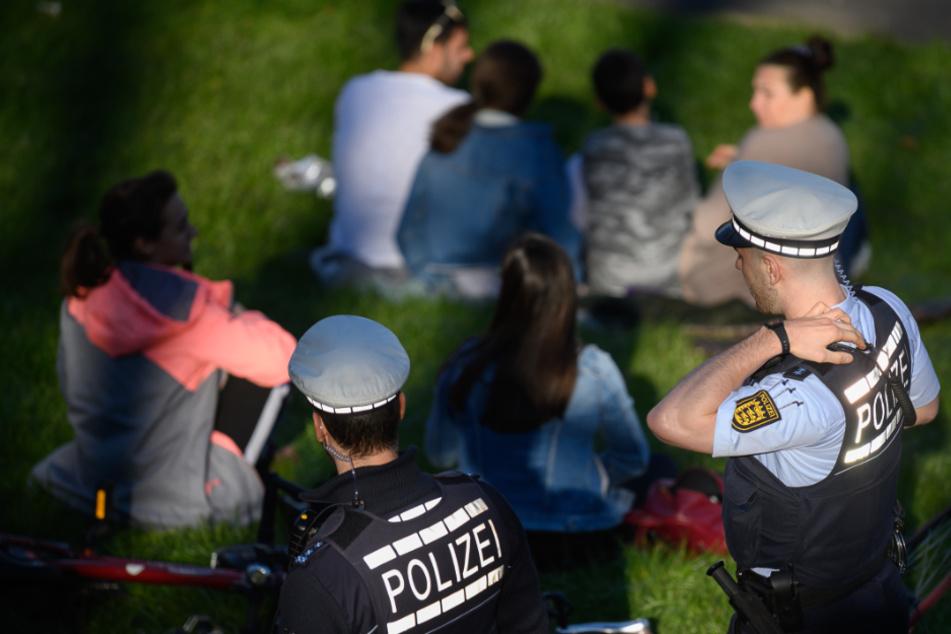 Polizeibeamte kontrollieren in einem Park die Einhaltung der Vorschriften zur Eindämmung des Coronavirus.