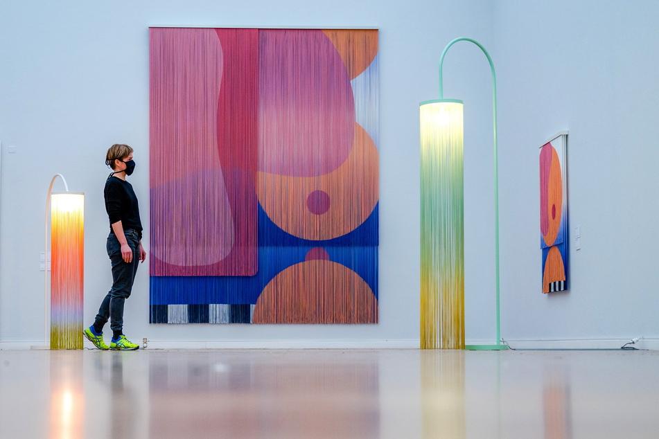 Hunderte Meter farbiger Fäden sind in mehreren Lagen zu Bildobjekten geschichtet. Auch der Schein der Lampen ist so eingehüllt.
