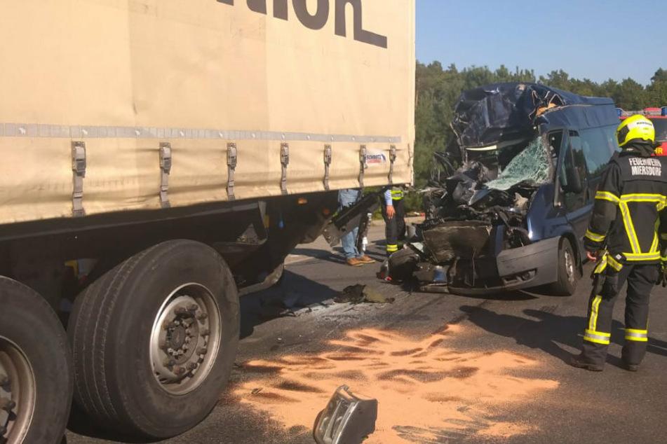 Das Wrack des Ford Transit steht hinter dem Sattelschlepper, auf den er aufgefahren war. Bei den Ausmaßen der Zerstörung ist es beinahe ein Wunder, dass die Fahrerin mit einem Schock davon gekommen ist. Ihr 56-jähriger Beifahrer hatte leider weniger Glück. Der Rollstuhlfahrer verstarb noch am Unfallort.