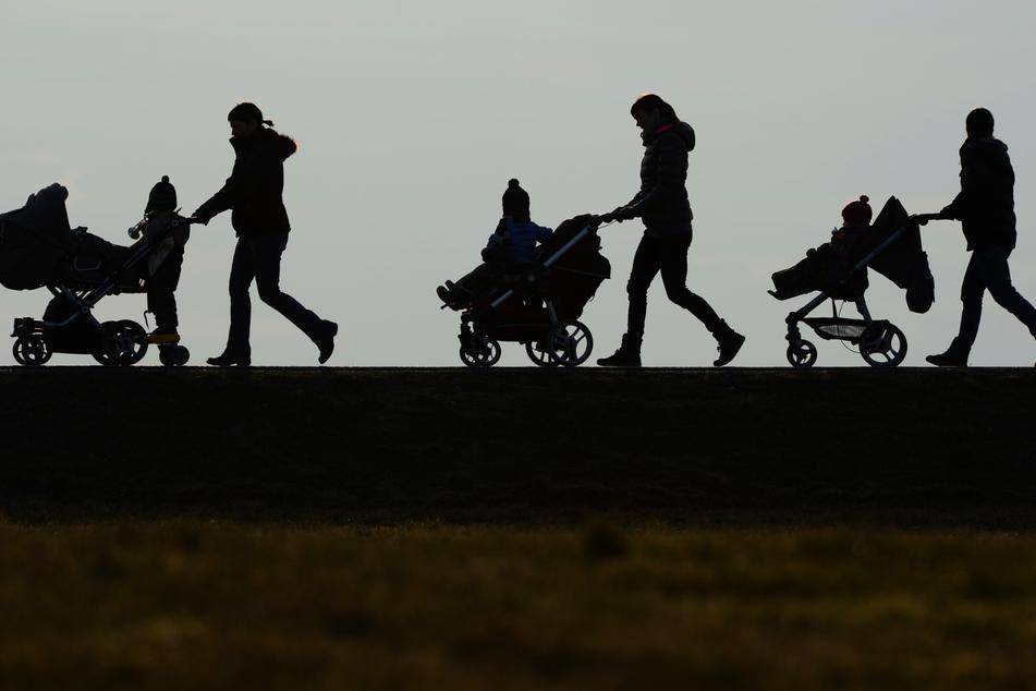 Drei Mütter schieben ihre Kinderwagen eine Landstraße entlang.