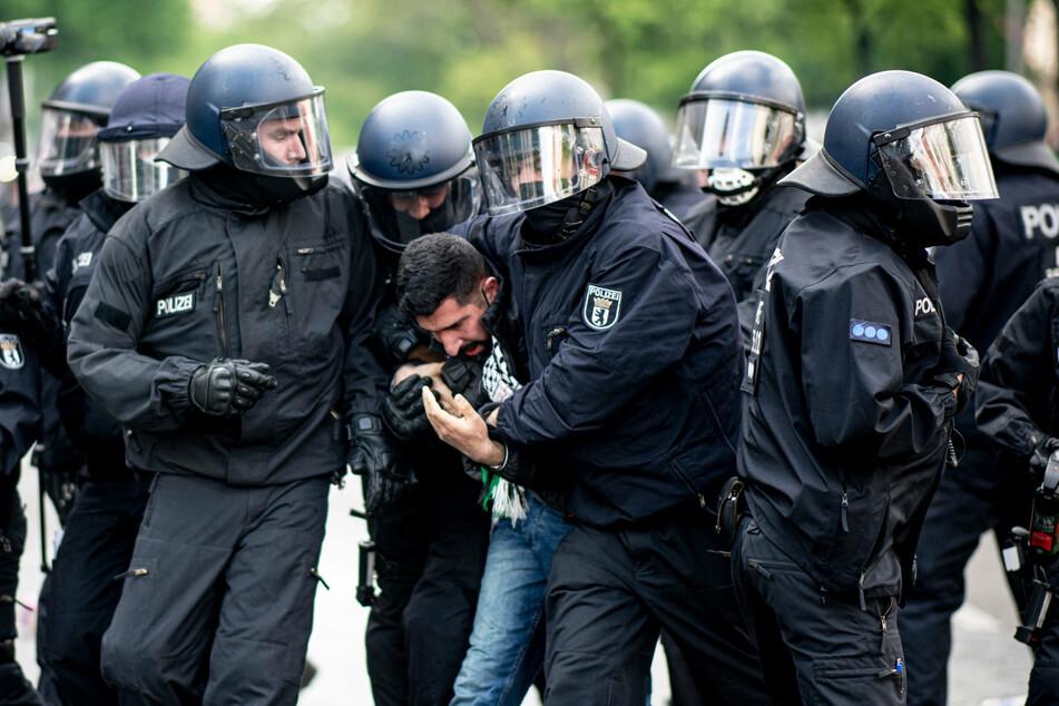 Die Polizei hält einen Teilnehmer der Demonstration verschiedener palästinensischer Gruppen in Neukölln fest.